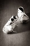 old-baby-shoes-worn-floor-concept-poor-childhood-35520443